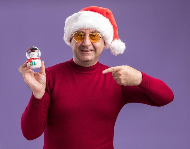 Homem de meia-idade feliz usando chapéu de papai noel de natal em óculos amarelos segurando um globo de neve de natal apontando com o dedo indicador para ele, de pé sobre um fundo roxo