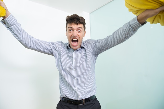 Homem de meia idade furioso levantando dois travesseiros