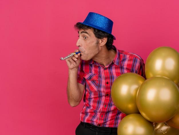 Homem de meia-idade impressionado com chapéu de festa e segurando balões, olhando para o lado soprando soprador de festa isolado na parede carmesim
