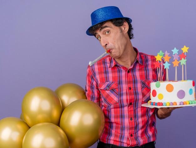 Homem de meia-idade impressionado com chapéu de festa segurando balões e soprando bolo de aniversário olhando para frente isolado na parede roxa