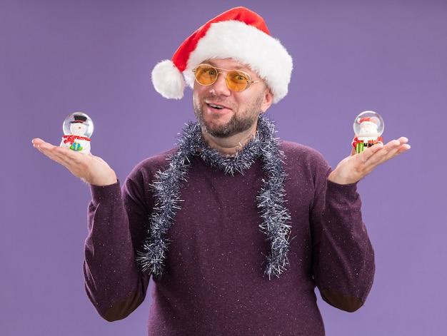 Homem de meia-idade impressionado com chapéu de papai noel e guirlanda de ouropel no pescoço, óculos segurando boneco de neve e estatuetas de papai noel isoladas na parede roxa