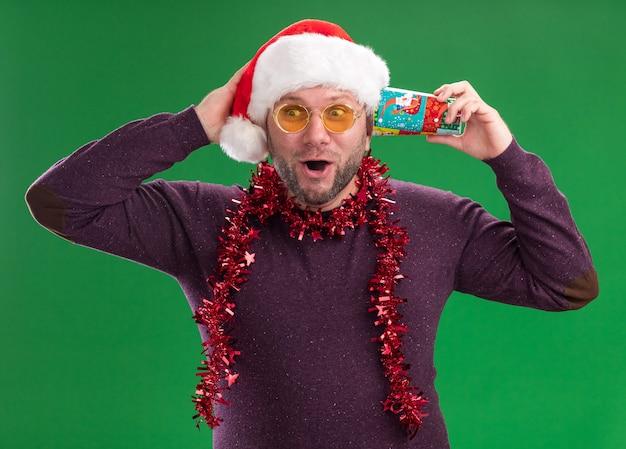 Homem de meia-idade impressionado com chapéu de papai noel e guirlanda de ouropel no pescoço, óculos segurando um copo de natal de plástico próximo à orelha, ouvindo segredos segurando a mão