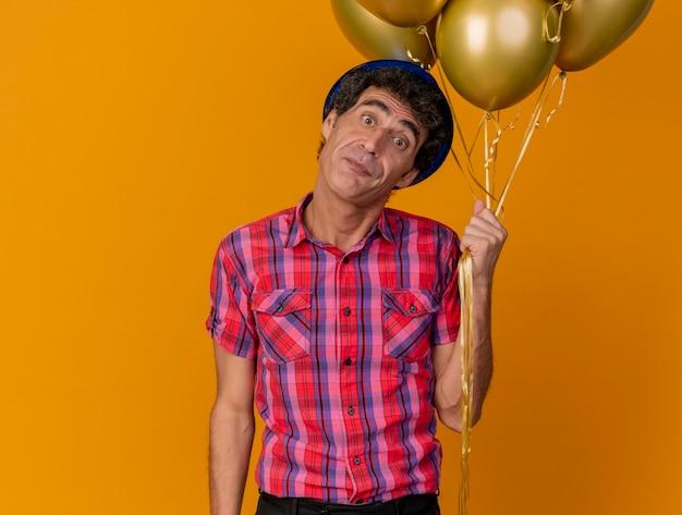 Homem de meia-idade impressionado com um chapéu de festa e segurando balões olhando para a frente, isolado na parede laranja