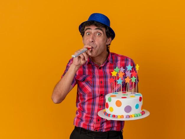 Homem de meia-idade impressionado com um chapéu de festa segurando um bolo de aniversário soprando um soprador de festa olhando para a frente, isolado na parede laranja
