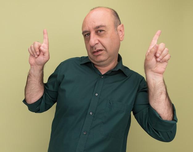 Homem de meia-idade impressionado com uma camiseta verde apontando para cima, isolado em uma parede verde oliva