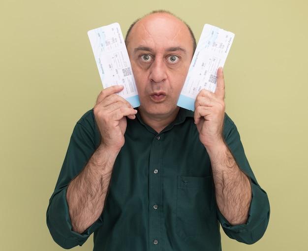 Homem de meia-idade impressionado, vestindo uma camiseta verde, segurando os ingressos ao redor do rosto, isolado na parede verde oliva