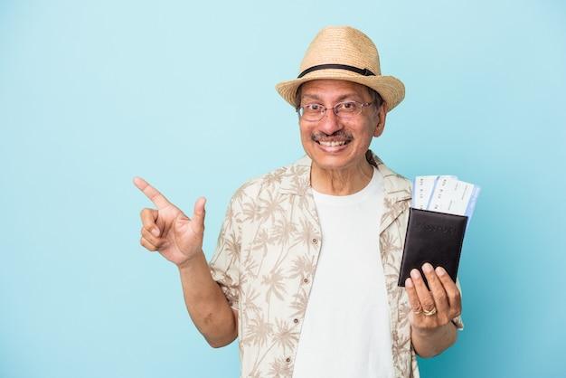 Homem de meia idade indiano do viajante sênior segurando o passaporte isolado no fundo azul, sorrindo e apontando de lado, mostrando algo no espaço em branco.