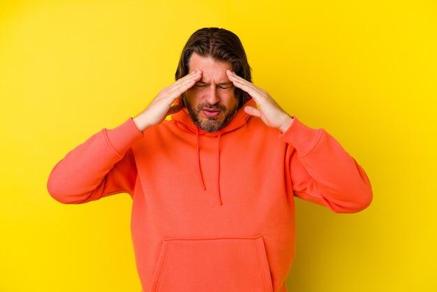 Homem de meia-idade isolado em uma parede amarela com dor de cabeça e tocando a parte frontal do rosto