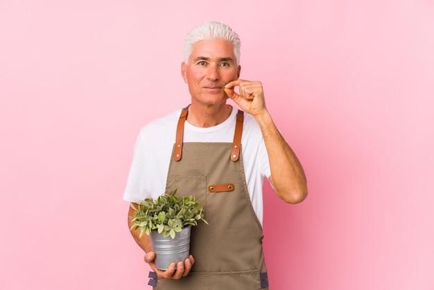Homem de meia idade jardineiro isolado com os dedos nos lábios, mantendo um segredo.