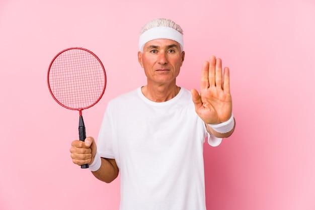 Homem de meia idade jogando badminton isolado em pé com a mão estendida, mostrando o sinal de pare, impedindo você.