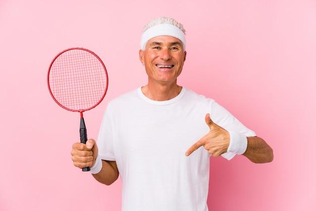 Homem de meia idade jogando badminton isolado pessoa apontando à mão para um espaço de cópia de camisa, orgulhoso e confiante