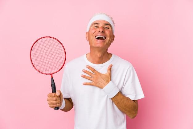 Homem de meia idade jogando badminton isolado ri alto, mantendo a mão no peito.