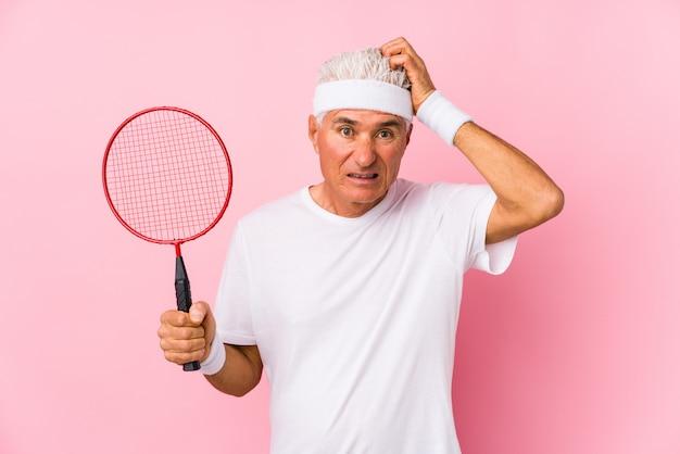 Homem de meia idade jogando badminton isolado sendo chocado, ela lembrou importante reunião.