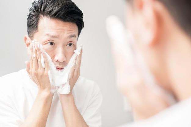 Homem de meia-idade lavando o rosto com espuma na pia