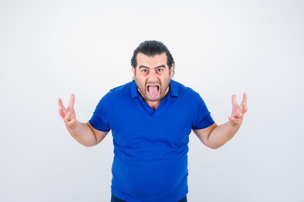 Homem de meia idade mantendo as mãos de maneira agressiva enquanto mostra a língua em uma camiseta pólo e parece zangado. vista frontal.