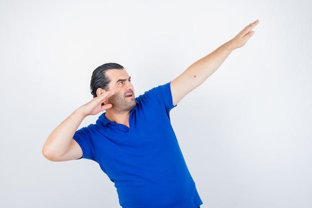 Homem de meia idade mirando com esticando as mãos em t-shirt azul e olhando focado. vista frontal.