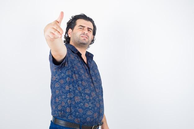 Homem de meia idade mostrando gesto de arma na camisa e parecendo confiante. vista frontal.