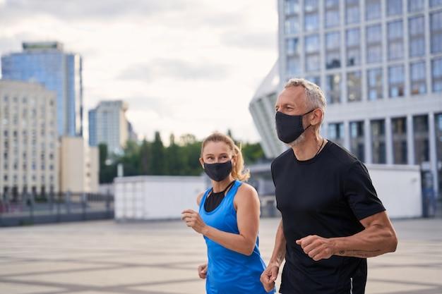 Homem de meia-idade motivado com máscara protetora correndo junto com a esposa em um ambiente urbano