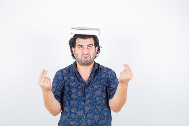 Homem de meia idade na camisa segurando o livro na cabeça enquanto mostra o gesto de dinheiro e olhando hesitante, vista frontal.