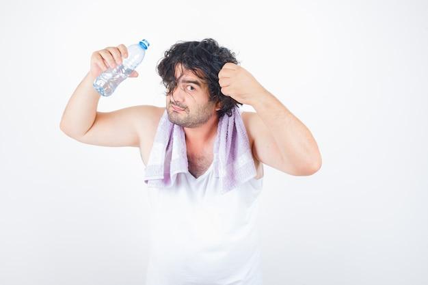 Homem de meia idade na parte superior do tanque, toalha segurando a mecha de cabelo, mantendo a garrafa de água e olhando engraçado, vista frontal.