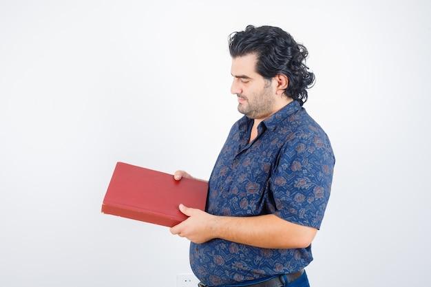Homem de meia idade olhando para um livro na camisa e olhando pensativo. vista frontal.