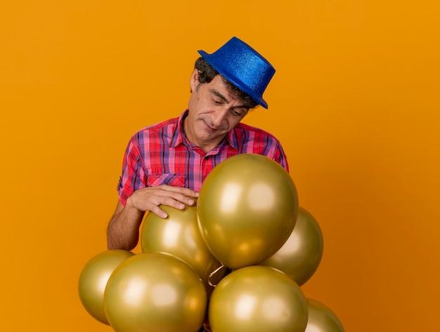 Homem de meia-idade pensativo e festeiro com chapéu de festa em pé atrás de balões, olhando para eles, colocando a mão em um deles isolado na parede laranja com espaço de cópia