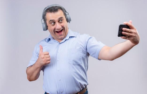 Homem de meia-idade positivo com camisa listrada vertical azul usando fones de ouvido, rindo e fazendo selfie em seu telefone em um fundo branco