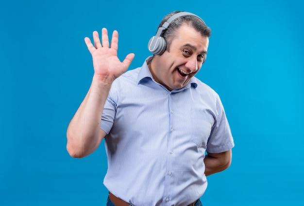 Homem de meia-idade positivo e alegre, com camisa listrada azul e fones de ouvido, mostrando gesto de mais cinco em um fundo azul