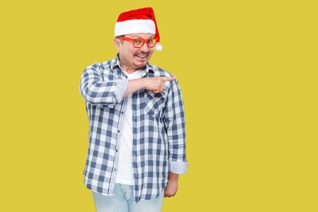 Homem de meia idade positivo na tampa vermelha, óculos e camisa quadriculada em pé e apontando o dedo para o espaço vazio da cópia e sorrindo, olhando para a câmera. foto de estúdio, isolada em fundo amarelo