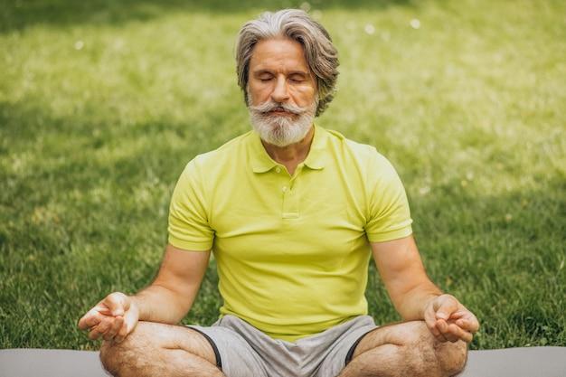 Homem de meia idade praticando ioga no tapete no parque