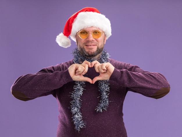 Homem de meia-idade satisfeito com chapéu de papai noel e guirlanda de ouropel no pescoço, óculos fazendo sinal de coração isolado na parede roxa