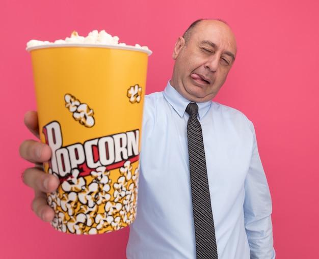 Homem de meia-idade satisfeito, vestindo uma camiseta branca com gravata, segurando um balde de pipoca para a câmera isolada na parede rosa