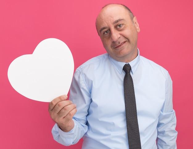 Homem de meia-idade satisfeito vestindo uma camiseta branca com gravata segurando uma caixa em formato de coração isolada na parede rosa