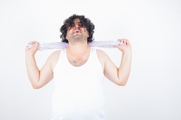 Homem de meia idade segurando a toalha no pescoço em um top, toalha e parecendo feliz, vista frontal.