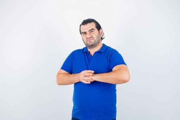 Homem de meia idade segurando as mãos na frente dela em camiseta azul e parecendo rancoroso. vista frontal.