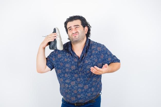 Homem de meia idade segurando o sapato por cima do ombro enquanto estica a mão em um gesto de questionamento na camisa e olhando hesitante, vista frontal.