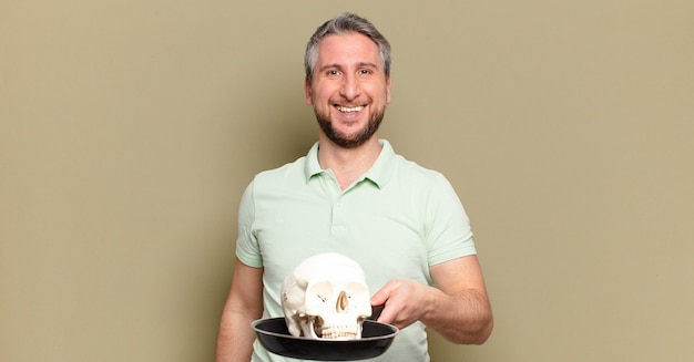 Homem de meia idade segurando um crânio humano
