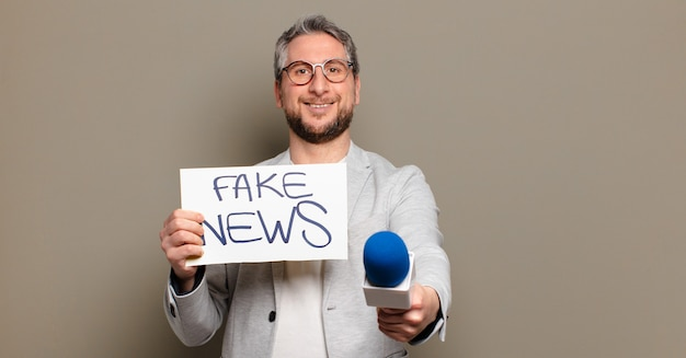 Homem de meia idade segurando um microfone e um quadro de notícias falso