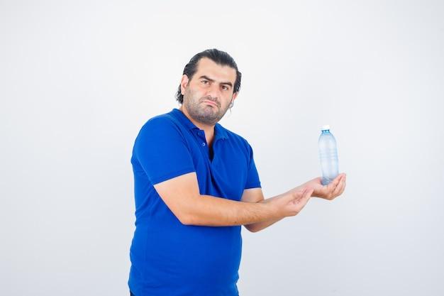 Homem de meia idade segurando uma garrafa de água enquanto espalha a palma da mão em uma camiseta polo e parece entediado, vista frontal.