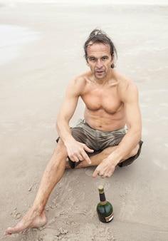 Homem de meia idade sentado na areia perto do mar e bebendo álcool
