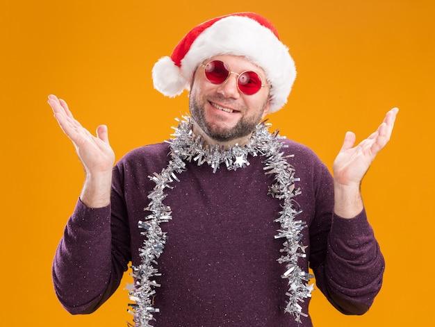 Homem de meia-idade sorridente com chapéu de papai noel e guirlanda de ouropel no pescoço, óculos mostrando as mãos vazias isoladas na parede laranja