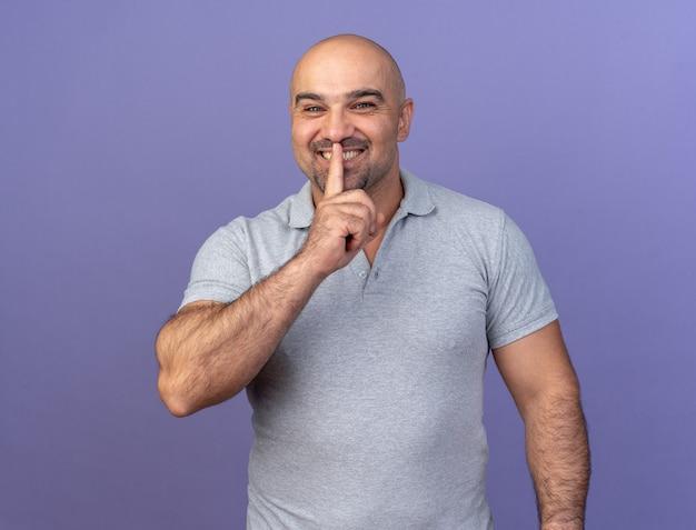 Homem de meia-idade sorridente e casual olhando para a frente fazendo gesto de silêncio isolado na parede roxa