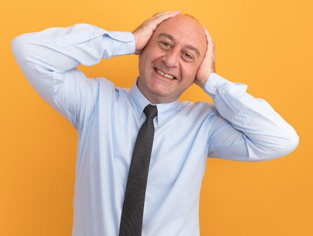 Homem de meia-idade sorridente, vestindo camiseta branca com gravata e colocando as mãos nas orelhas isoladas em uma parede laranja