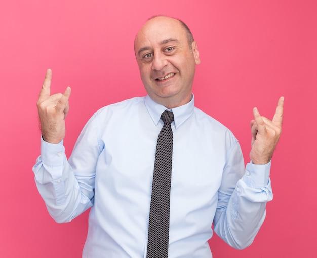 Homem de meia-idade sorridente, vestindo camiseta branca com gravata, mostrando gesto de cabra isolado na parede rosa