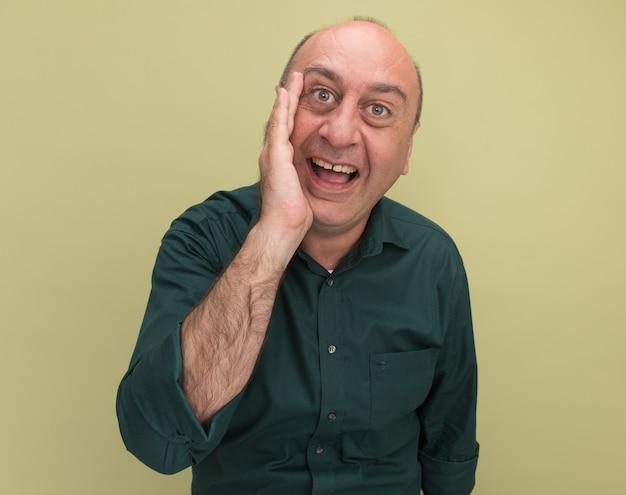 Homem de meia-idade sorridente, vestindo uma camiseta verde, ligando para alguém isolado na parede verde oliva