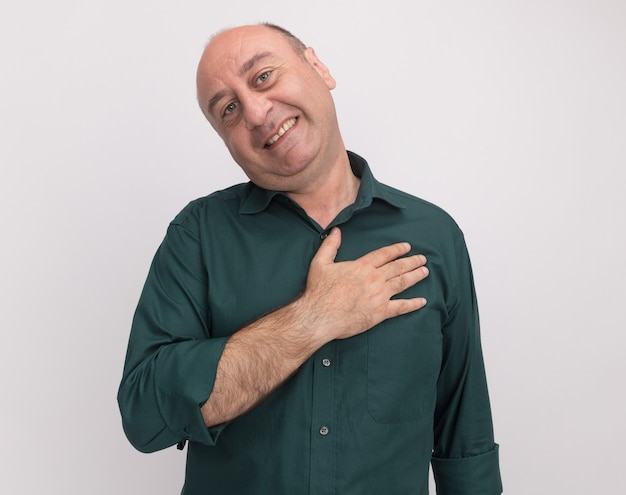 Homem de meia-idade, sorrindo, inclinando a cabeça e vestindo uma camiseta verde, colocando a mão no coração isolado na parede branca