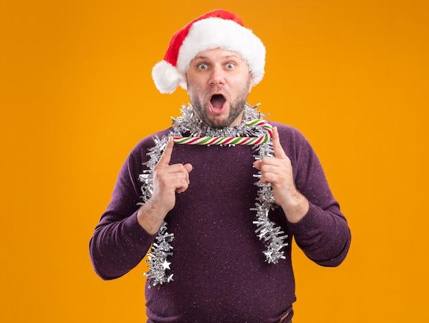 Homem de meia-idade surpreso com chapéu de papai noel e guirlanda de ouropel no pescoço, segurando a bengala de natal horizontalmente, olhando para a câmera isolada em fundo laranja