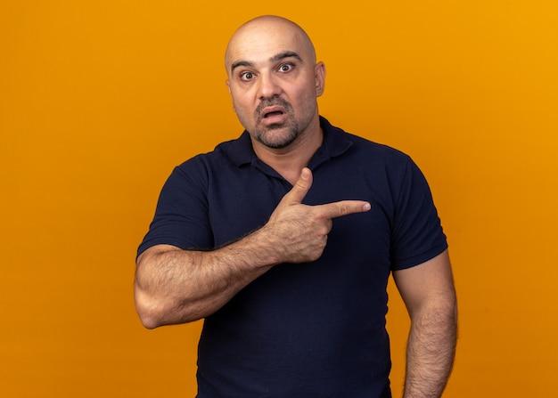 Homem de meia-idade surpreso e casual olhando para a frente, apontando para o lado isolado na parede laranja