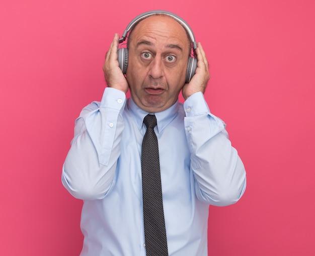Homem de meia-idade surpreso vestindo camiseta branca com gravata e fones de ouvido isolados na parede rosa