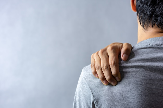 Homem de meia idade tem dor no ombro.